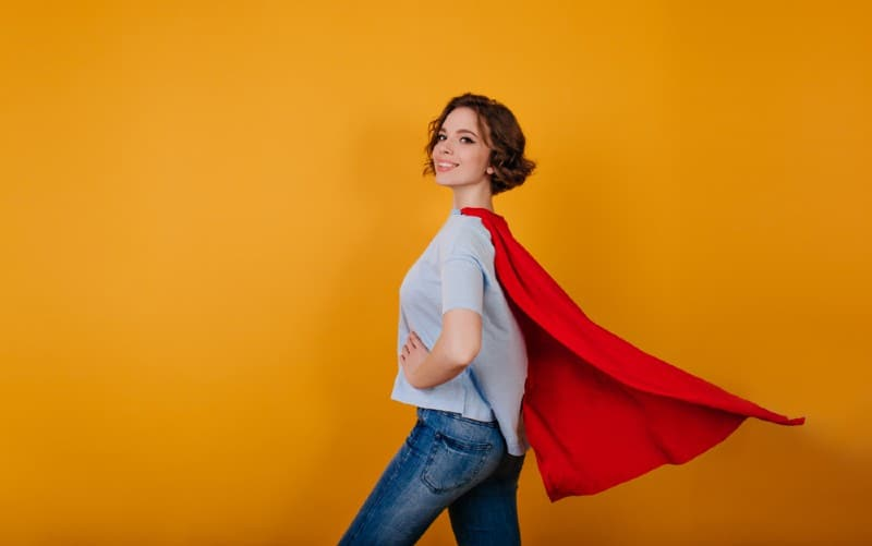 Smiling woman wearing blue jeans and superhero cape