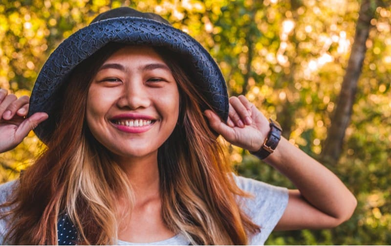 Smiling woman with hat in the forest durng daytime