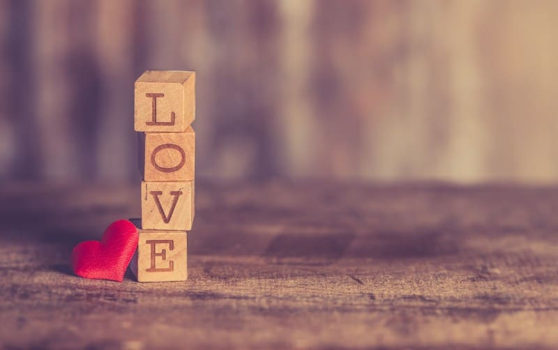 The word love written with a stack of wooden blocks and red heart