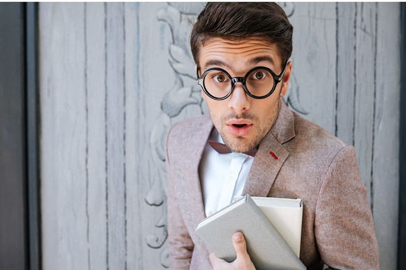 surprised geek man carrying books behind is a door