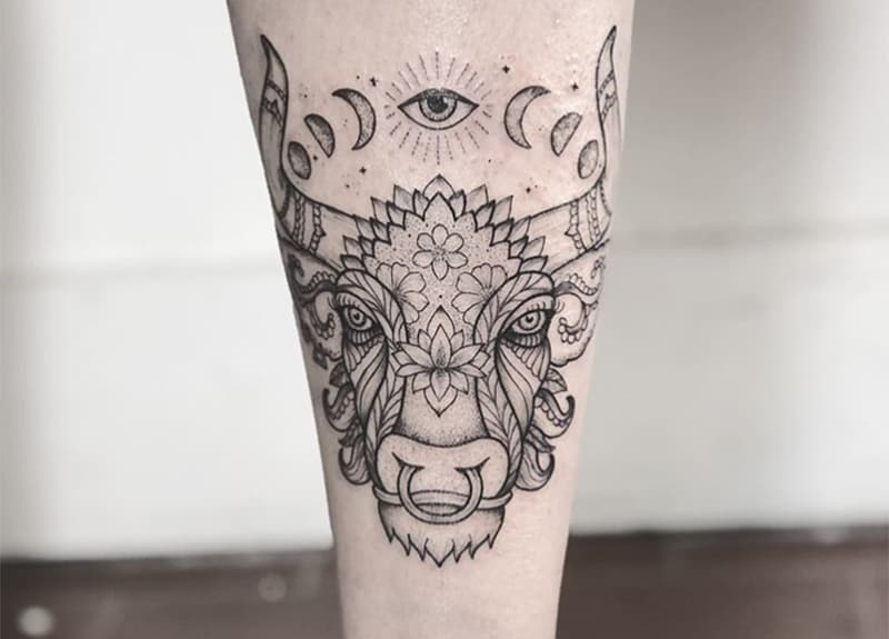 taurus tattoo with one eye above it with flowers design
