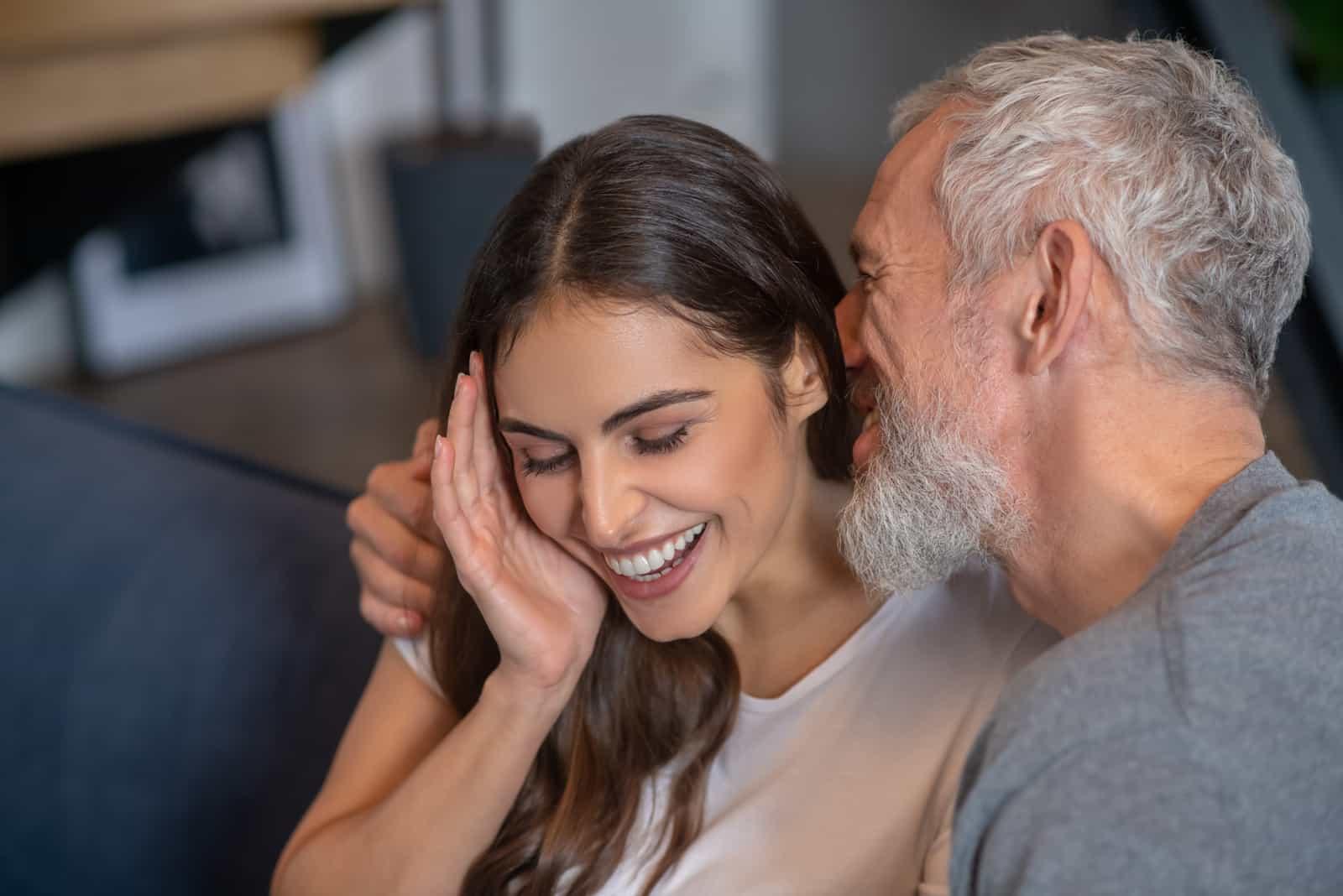 the older man whispers something in the brunette's ear