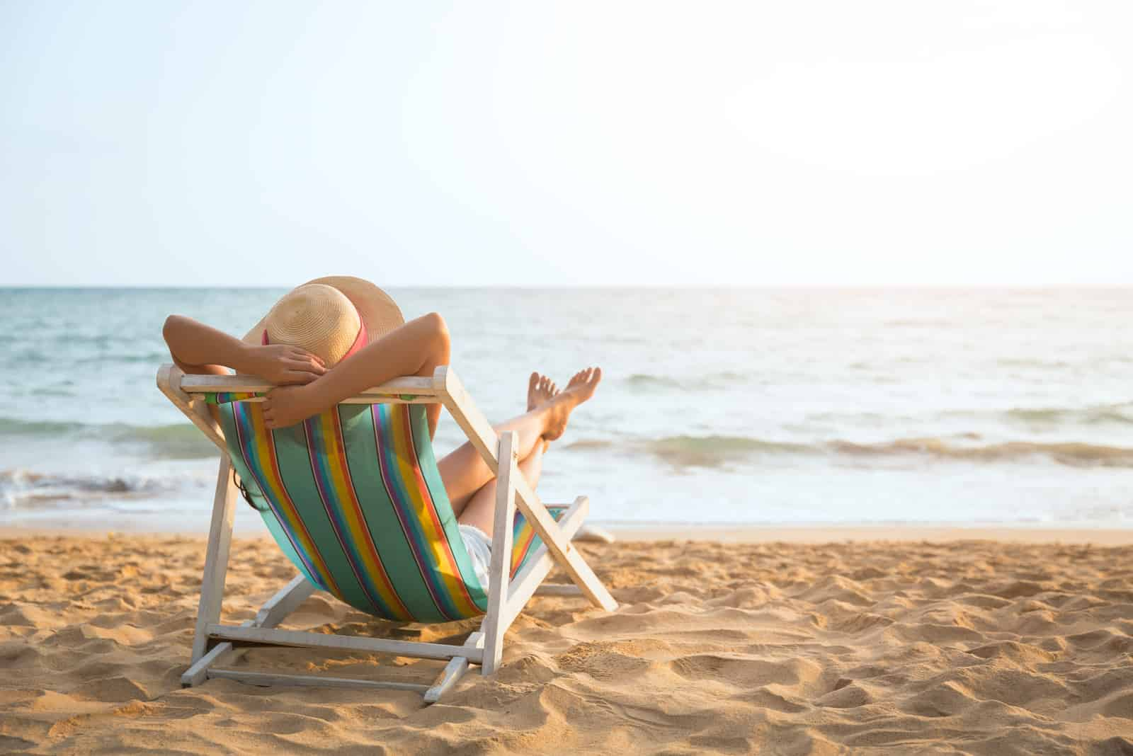 the woman is lying and the sun is on the beach