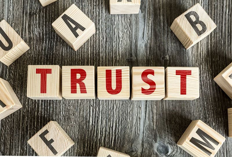 the word trust formed from the letter blocks along with some letters