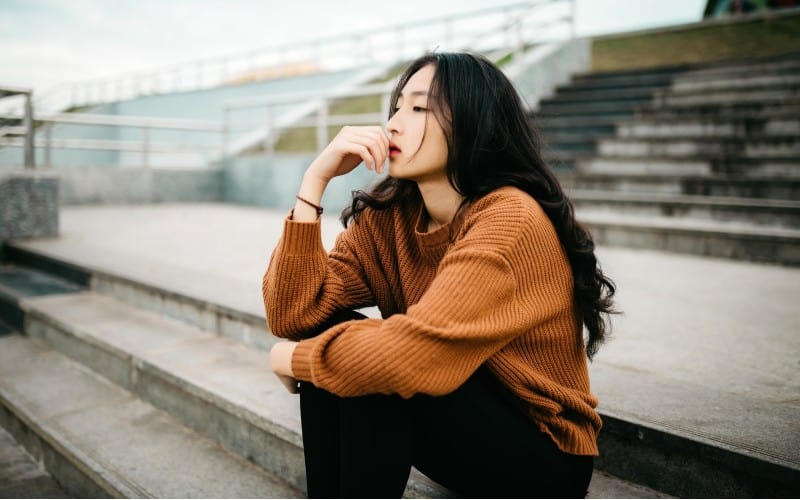 Thinking young asian woman sitting on stairs outdoors