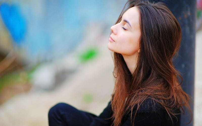 Thinking young woman with her eyes closed sitting outdoors
