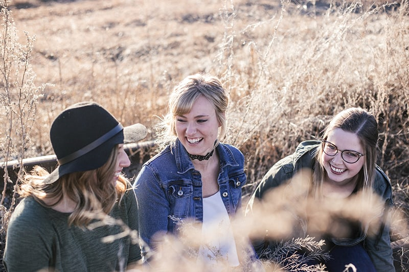 three women laughing in the field