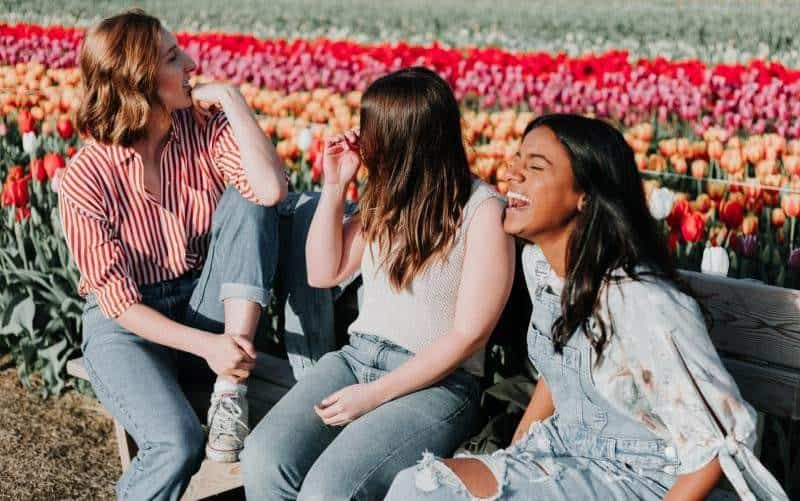 Young girls sitting on a bench near a tulip field during daytime