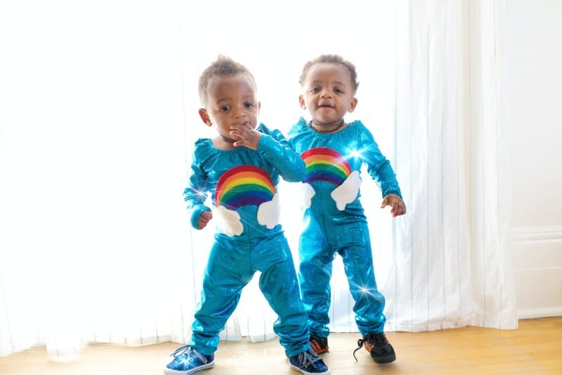 two male twins standing near white curtain
