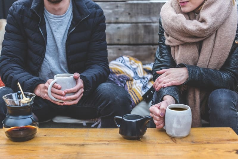two adults talking over cup of coffee