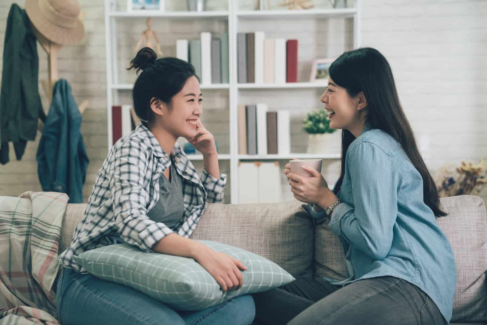 two girls sit on the sofa and talk