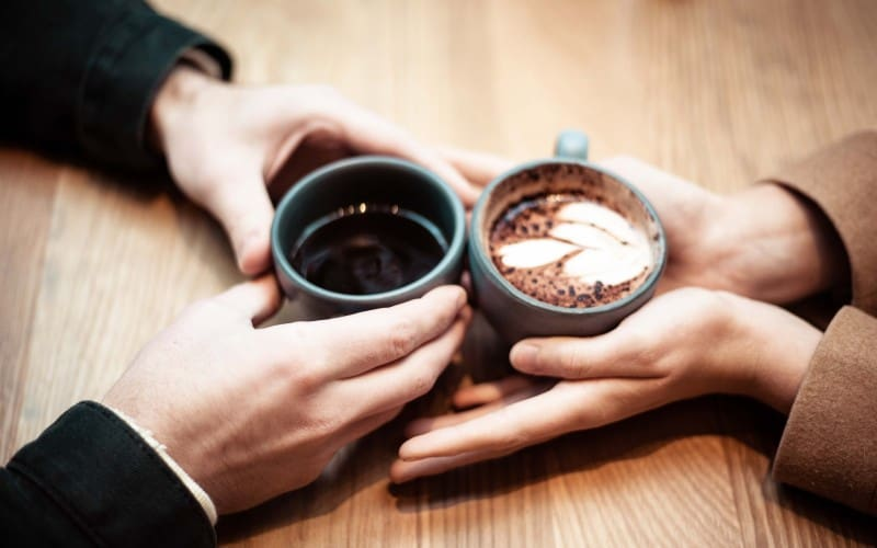 the hands of two person holding ceramic mugs with coffee on a brown table