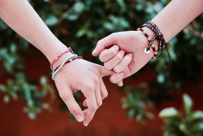 two person with bracelets holding pinky fingers