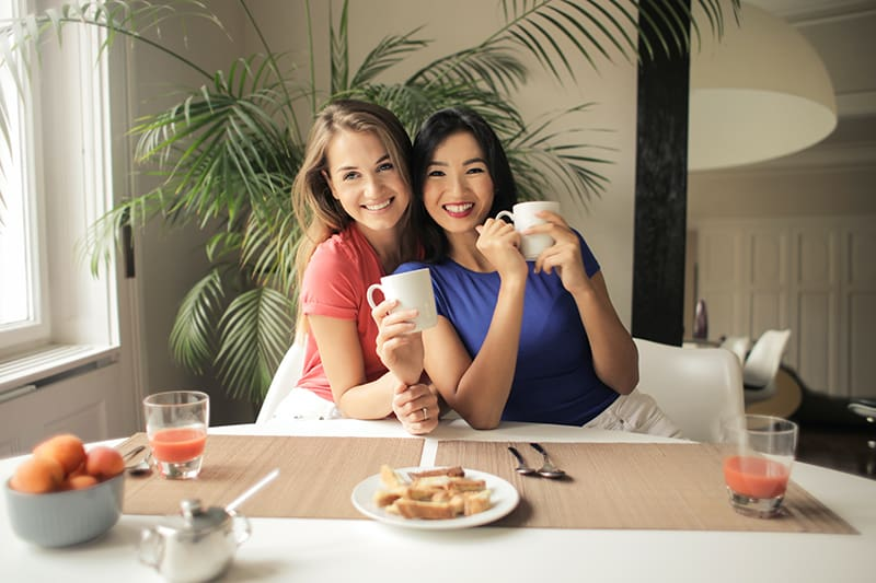 two women leaning on each other while holding white mugs
