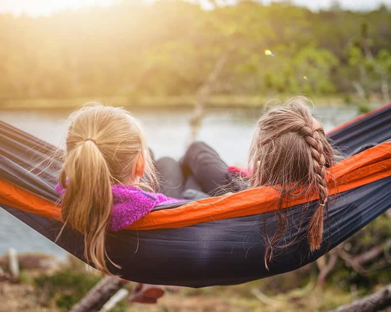 two women lying on hammock watching the river