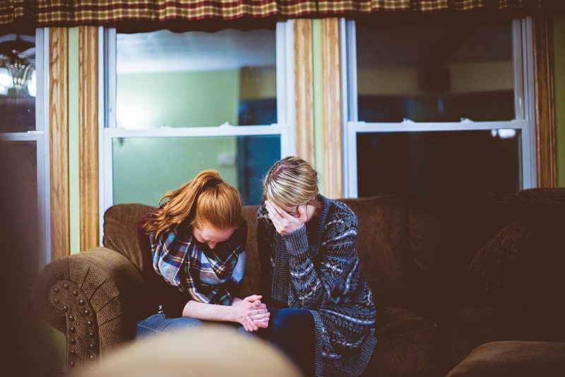 two women sitting on the couch while both crying