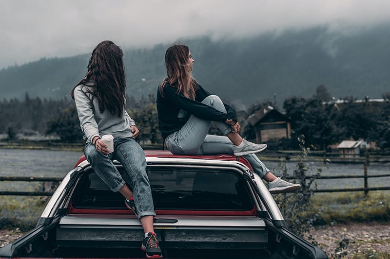 two women sitting on vehicle`s roof near lake