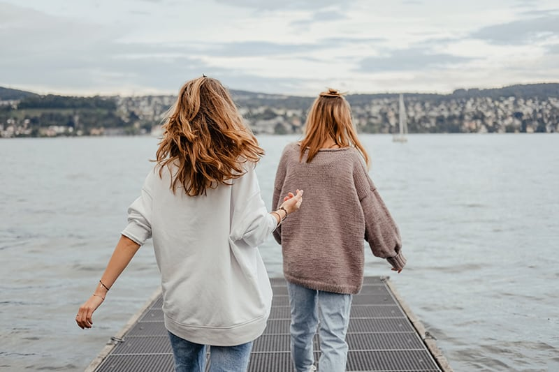 two women standing on dock front of the sea at daytime