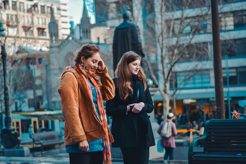 two women walking next to each other in the town