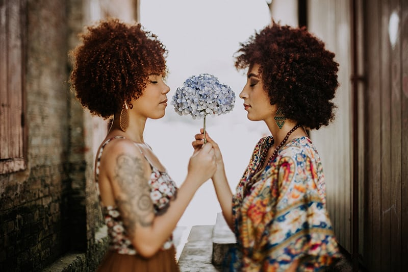 two women with afro hair holding flower together