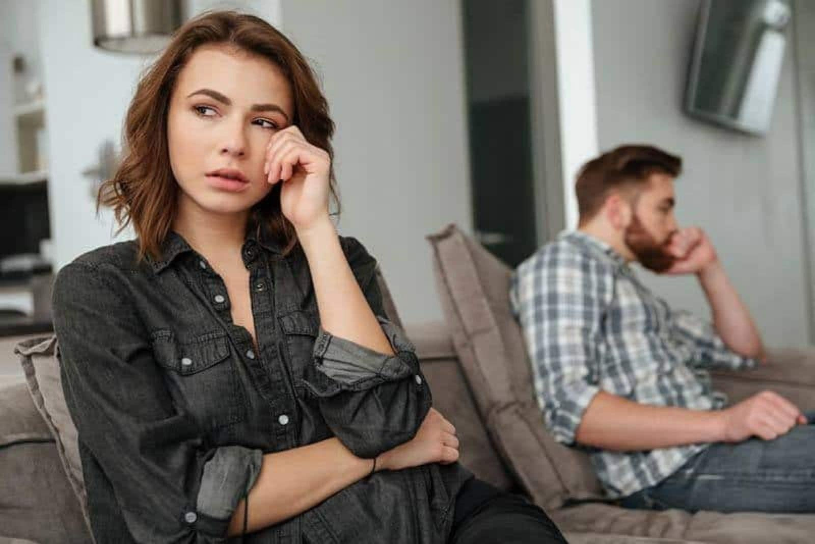 upset couple sitting in living room