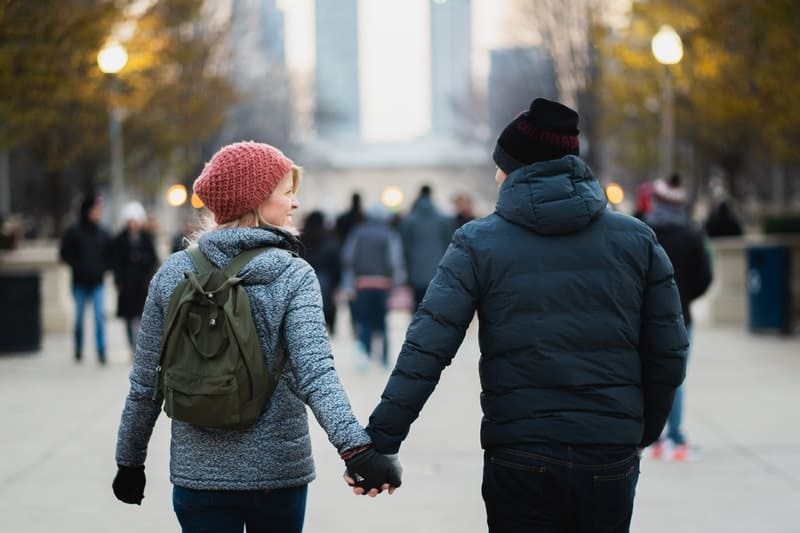 walking hand in hand couple wearing winter suits in public place