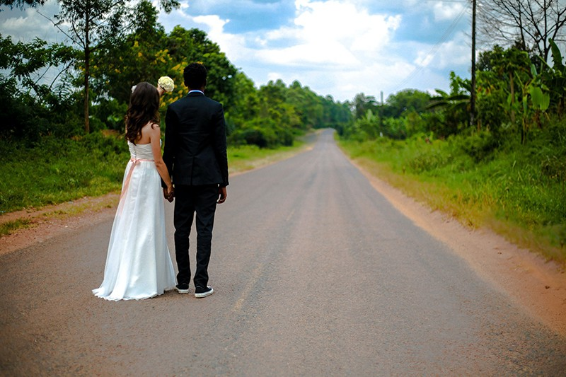 wedding couple standing on the road between trees