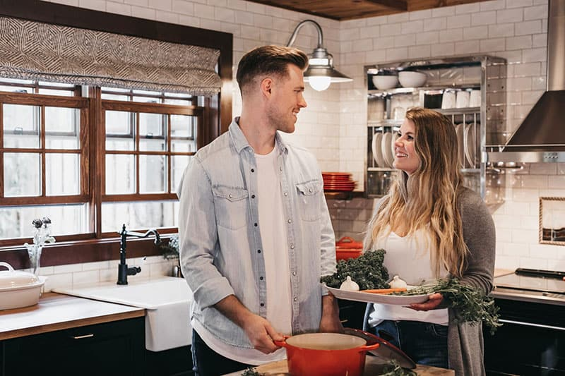Wife cooks dinner for happy husband