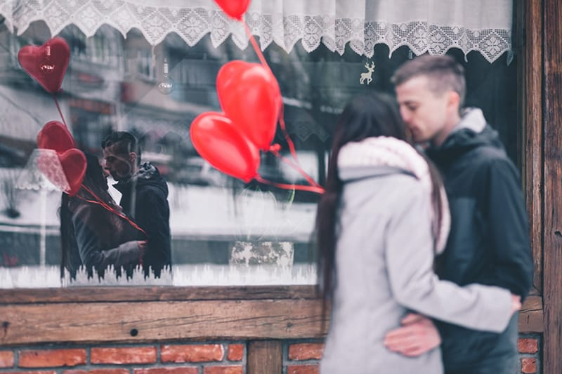 woman and man kissing in front of the store and holding red baloons