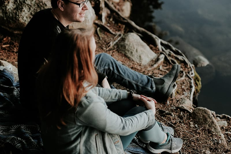 woman and man sitting near cliff while having conversation