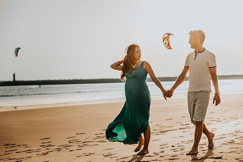 woman and man walking on beach while holding hands