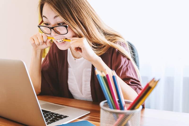 Woman biting pencil while staring at laptop