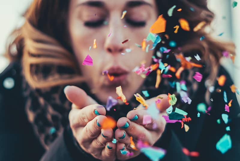 woman blowing paper strips from her palms