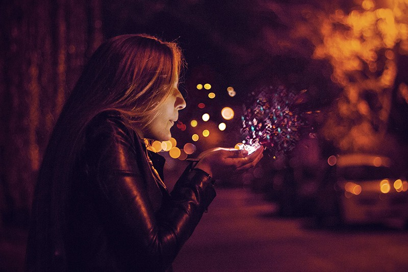 woman blowing sprinkle in her hand while standing in the night