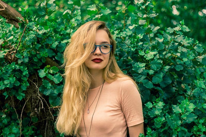 Woman with blue eyeglasses standing in front of plant wall