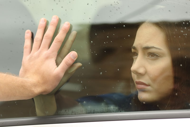 Woman behind car window while a man leans on it with a hand