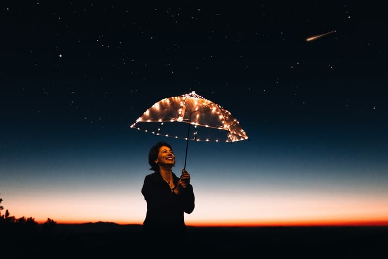 woman carrying umbrella with lights on a starry night