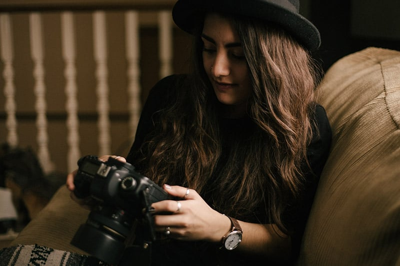 woman on couch holding camera