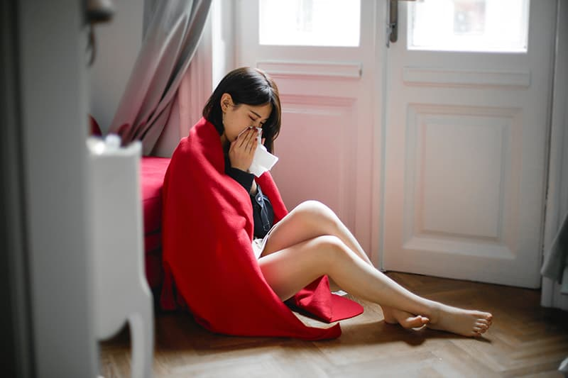 woman covered with red blancket sitting on the floor