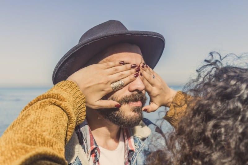 curly hair woman in yellow sweater covering man's eyes