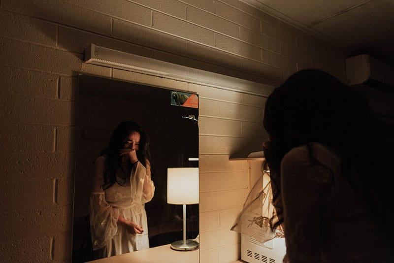 woman crying in front of the mirror with light coming from the lamp