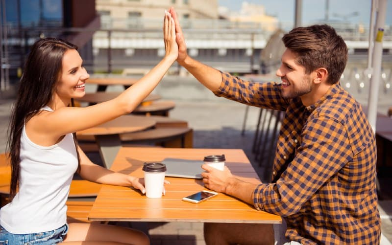 Happy woman giving high five to man while sitting at a table outdoors during daytime