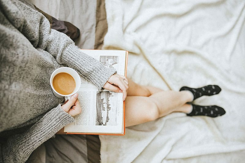 Woman in grey sweater holding coffee cup and reading a book