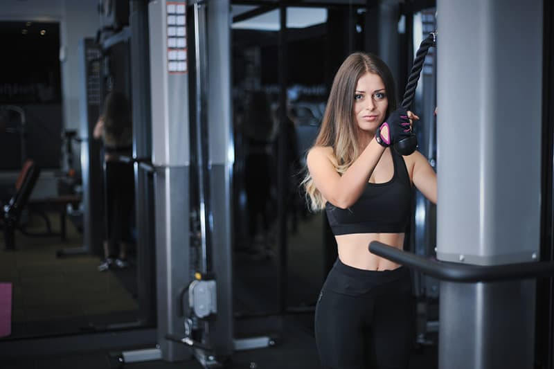 Woman at the gym standing in front of exercise equipment
