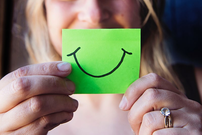 woman holding a green paper with smile drawn on it