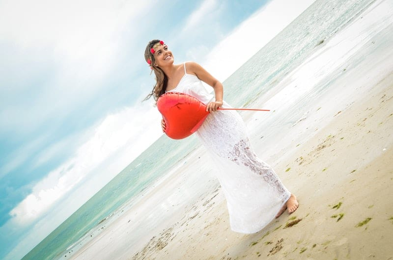 woman holding a heart shaped balloon in the seashore wearing flower crown and white dress