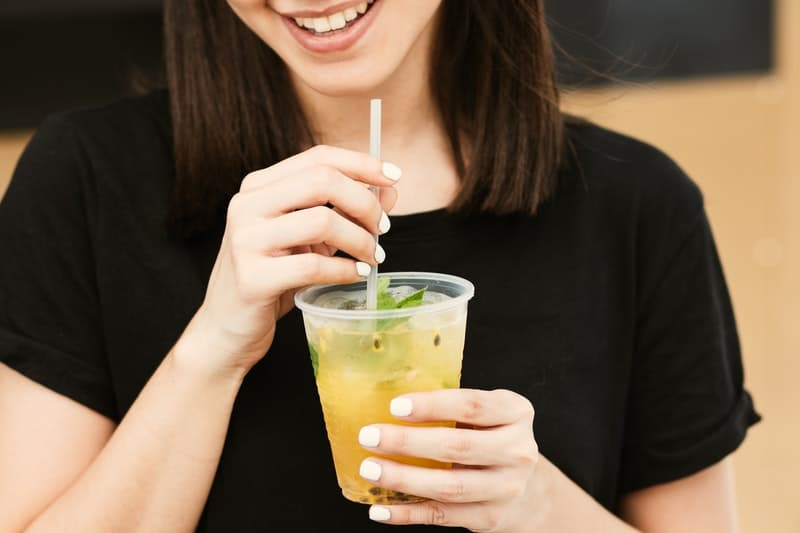 woman holding clear plastic cup with straw wearing black tshirt
