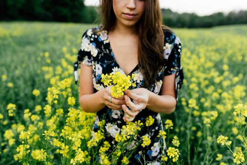 woman in floral dress holding yellow flowers outdoor