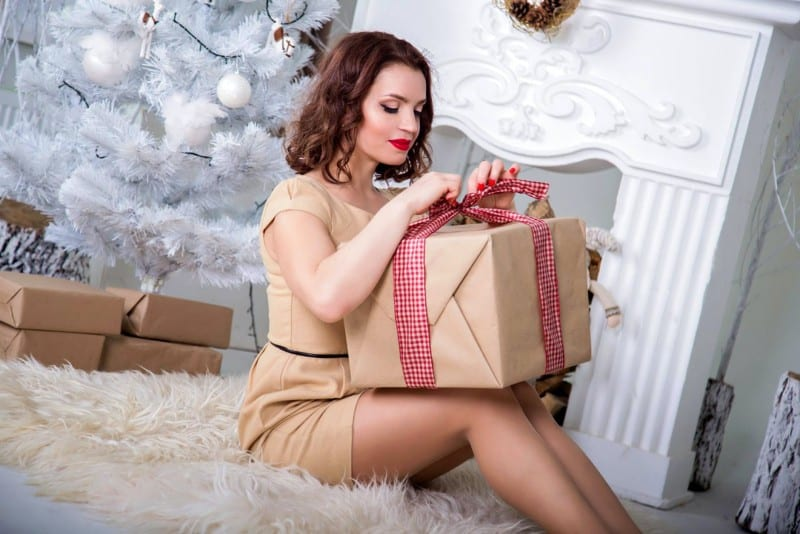 woman with red lipstick unwrapping gift
