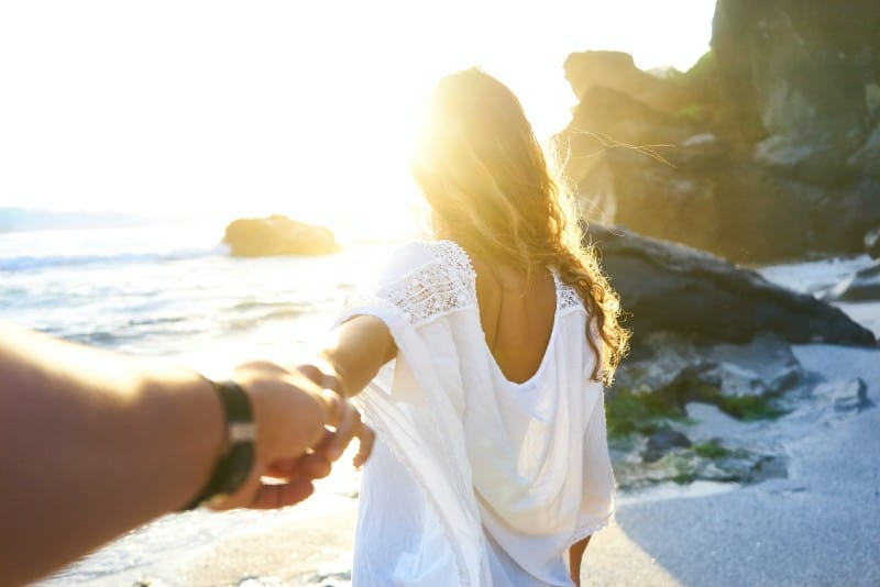 man holding woman's hand beside sea while facing sunlight
